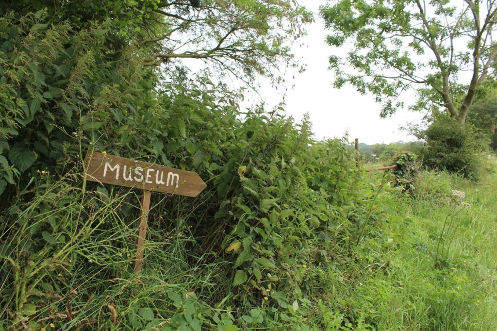 A wooden hand-painted sign for a museum standing in a bank of nettles