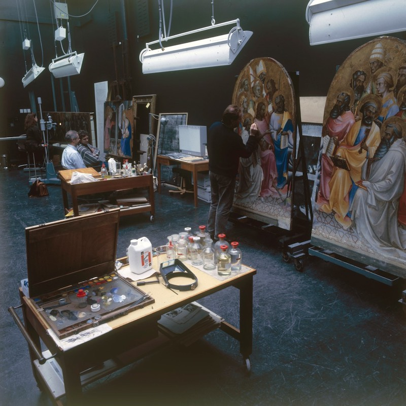 A conservation studio with paintings on easels and conservators working.
