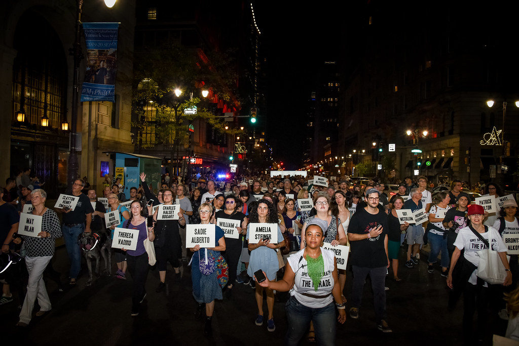 A large parade of people on a night-time street in Philadelphia. They carry placards bearing people's names.