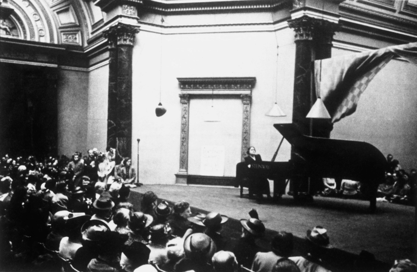 The pianist Myra Hess sits at a grand piano on a stage in front of a large audience at the National Gallery in London.