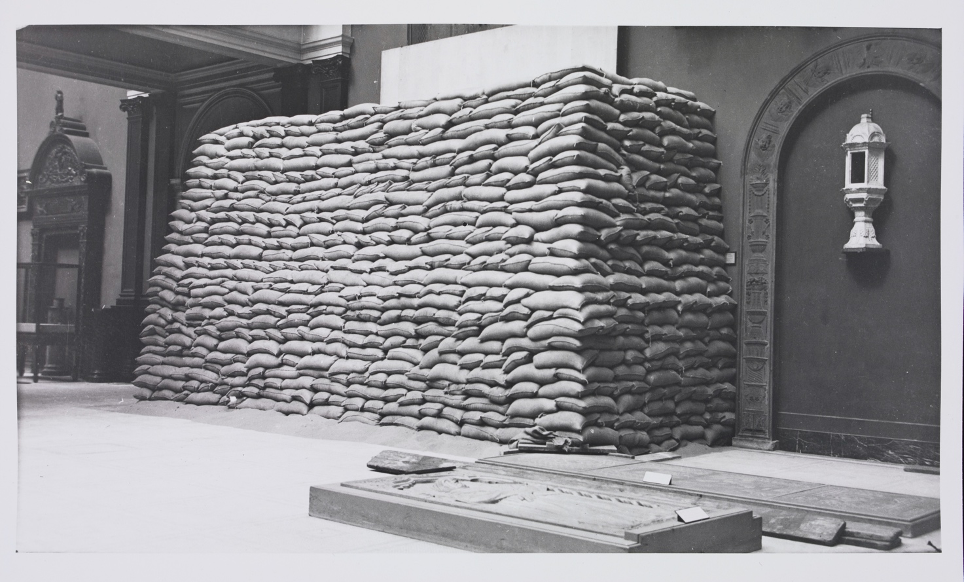 A gallery in the V&A Museum. A tall pile of sandbags covers half of the wall. Ornate doorways and other exhibits stand on either side.