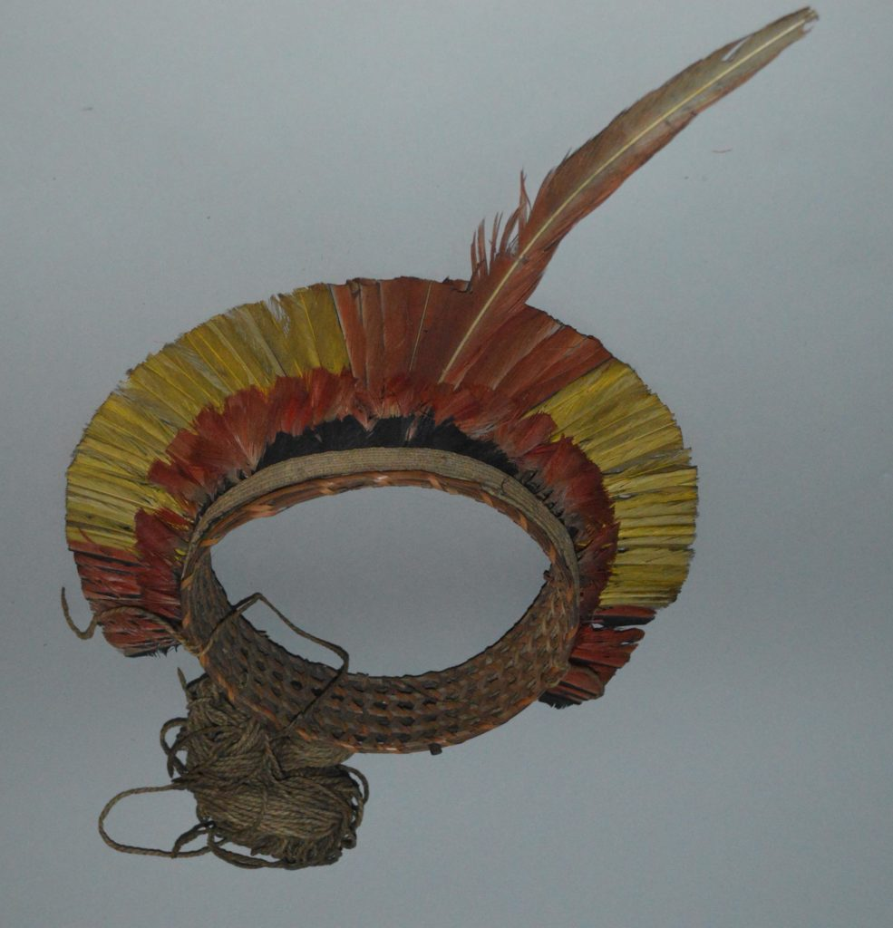 A headdress from Guyana made from reeds and yellow, red and black feathers that form a ring.