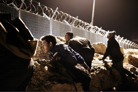 2012. Greece, Corinth. Mohamed from Morocco and his friends hiding behind the rocks at the port during the night, waiting for the right time to illegally board a ship to Italy. ### 2012. Corinto. Grecia. Mohamed del marocco con i suoi amici si nasconde dietro le rocce del porto, aspettando il momento giusto per entrare nella illegalmente sulla nave merce diretta verso L'Italia.